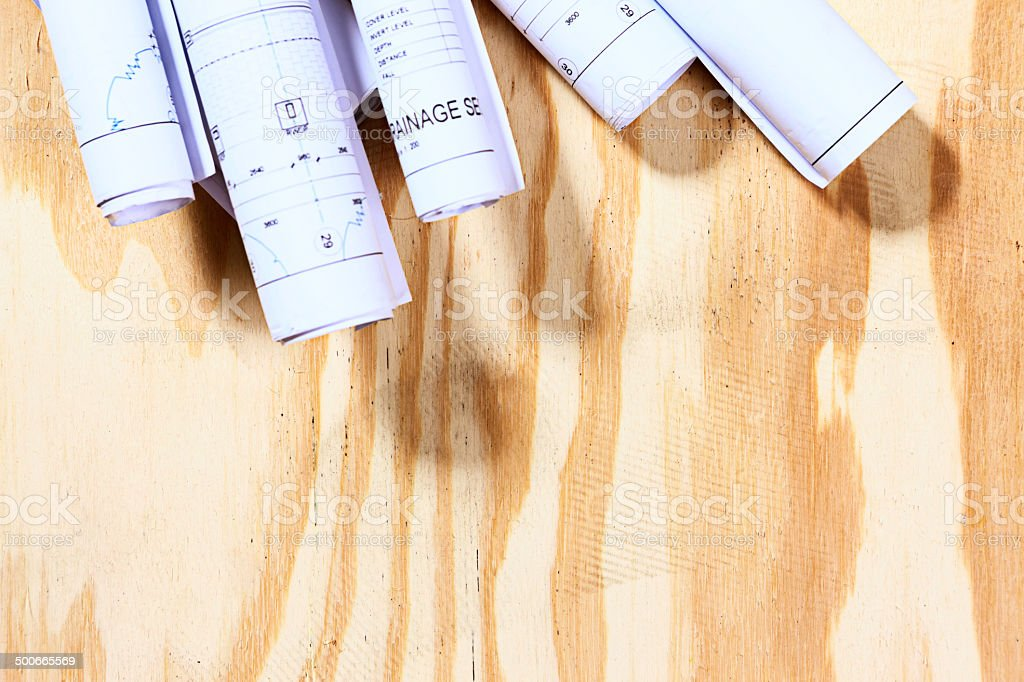 Rolled-up building plans form top border on wooden surface royalty-free stock photo