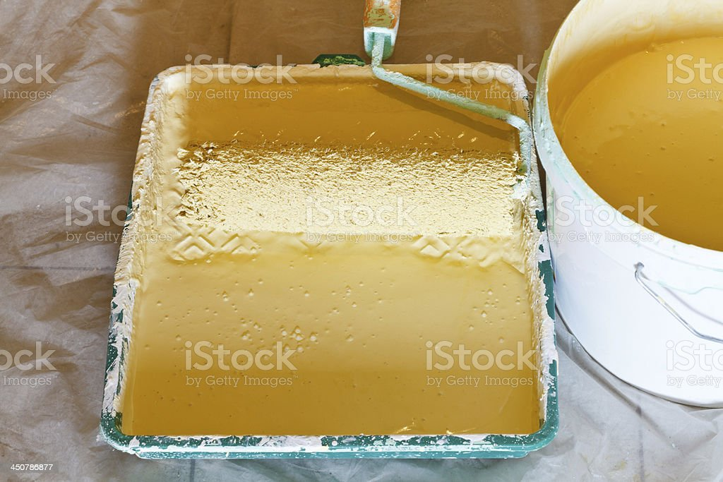 roller brush and bucket with yellow paint stock photo