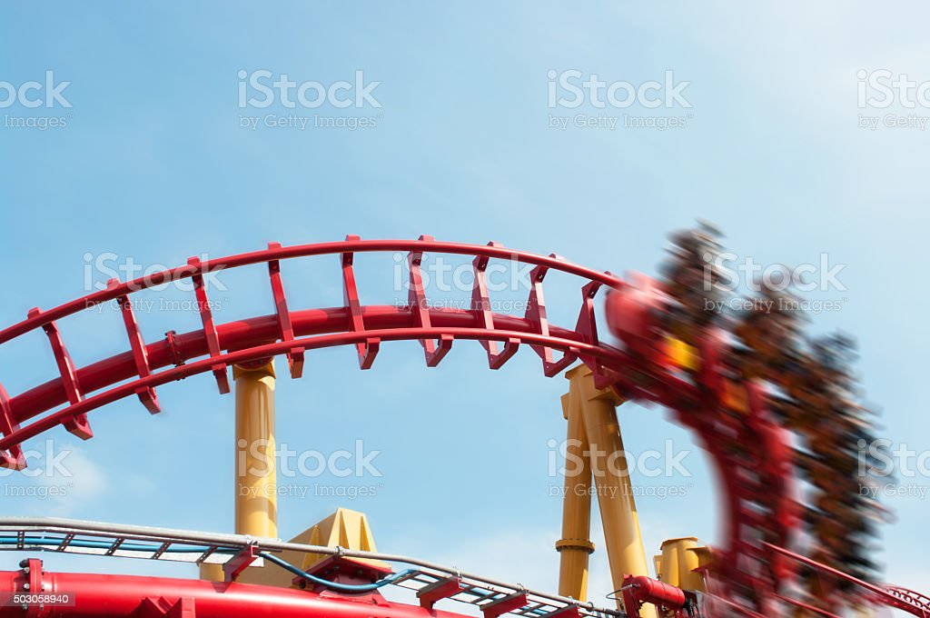 Roller coaster ride under blue sky with motion effect applied stock photo