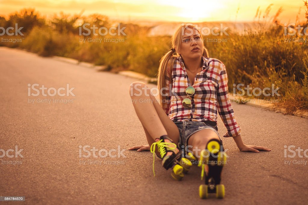 Roller skate girl sitting on the road stock photo