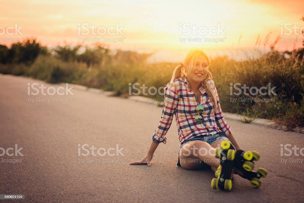 Roller skate girl sitting on the road stock photo