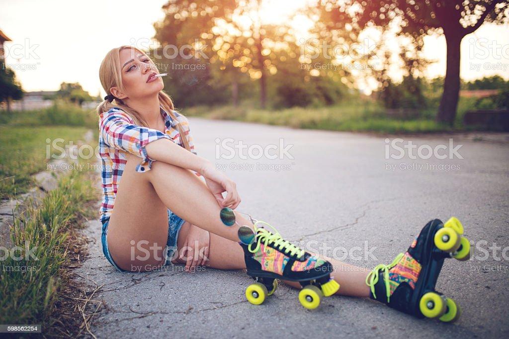 Roller skate girl smoking stock photo