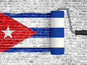 roller to paint on white brick wall with cuba flag