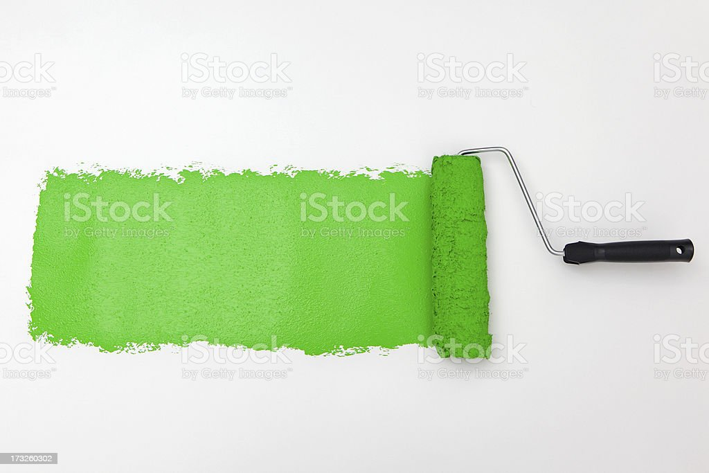Roller with green paint on white background stock photo