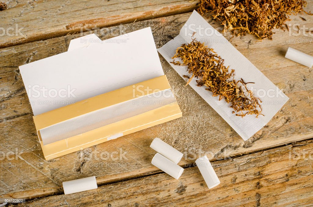 Rolling cigarettes stock photo