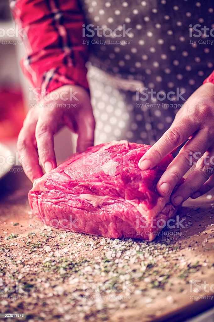 Rolling Fresh Roast Beef into Herbs and Spices stock photo
