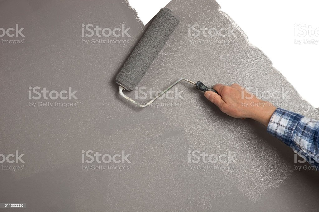 Rolling gray paint on white wall, copy space stock photo