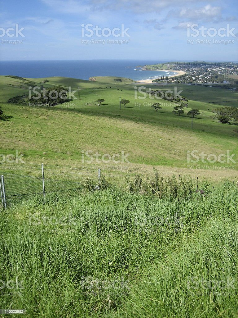 Rolling green hills outside of a town by the ocean  royalty-free stock photo
