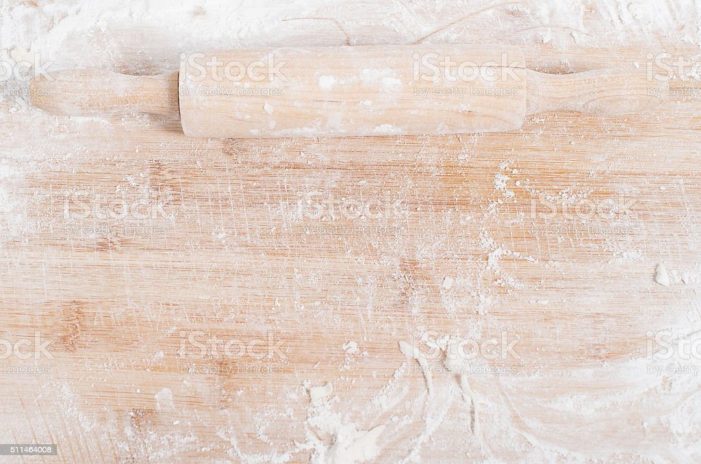 Rolling pin on a wooden tray covered with flour stock photo