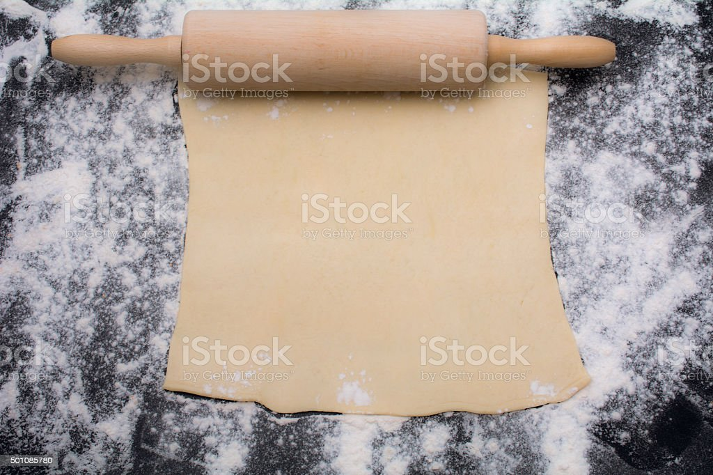 rolling pin with flour on black counter rolled out dough stock photo