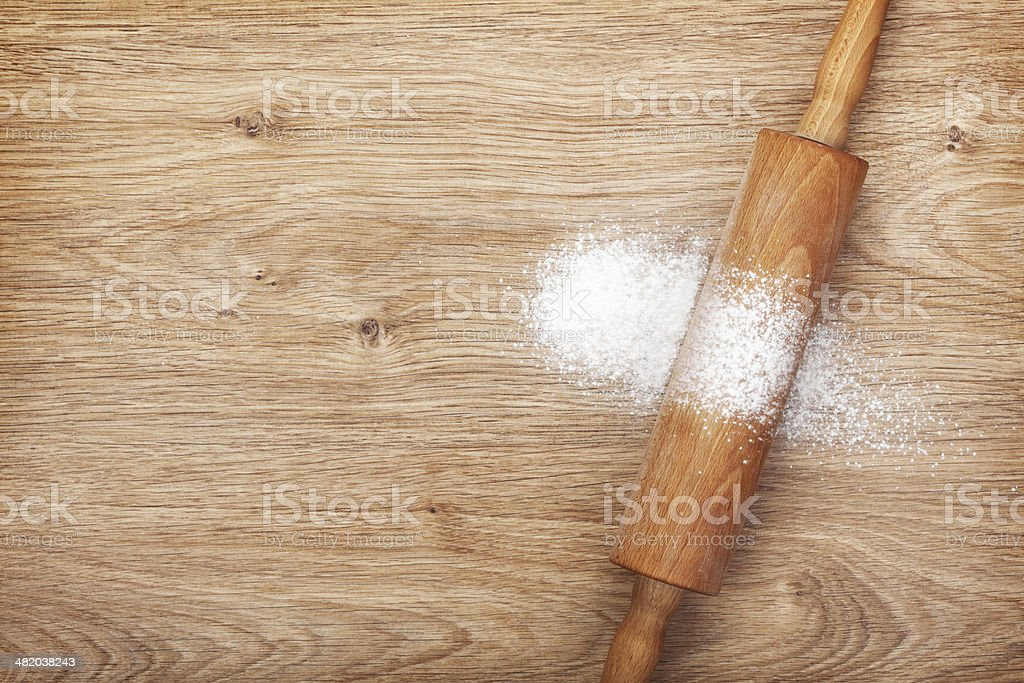 Rolling pin with flour on wooden table stock photo