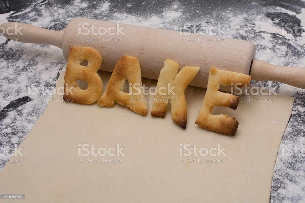 rolling pin with word bake  on black counter with dough stock photo
