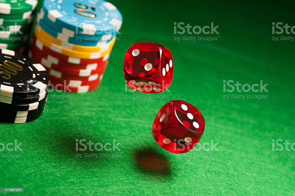 Rolling red dice on a casino table stock photo