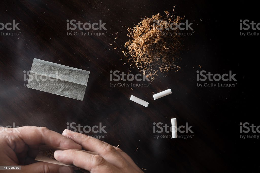 Rolling tobacco on wooden table stock photo