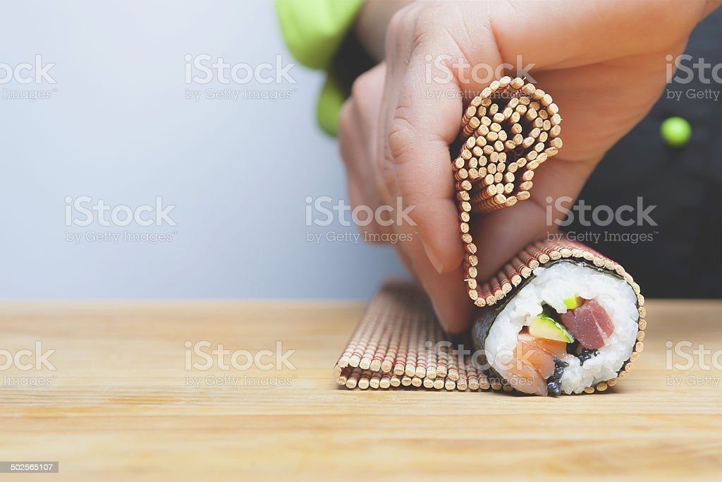 rolling up sushi stock photo