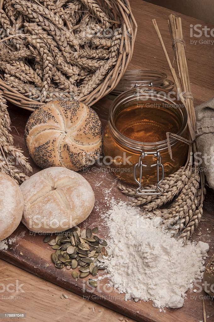 Rolls, bread and flour on wooden table royalty-free stock photo