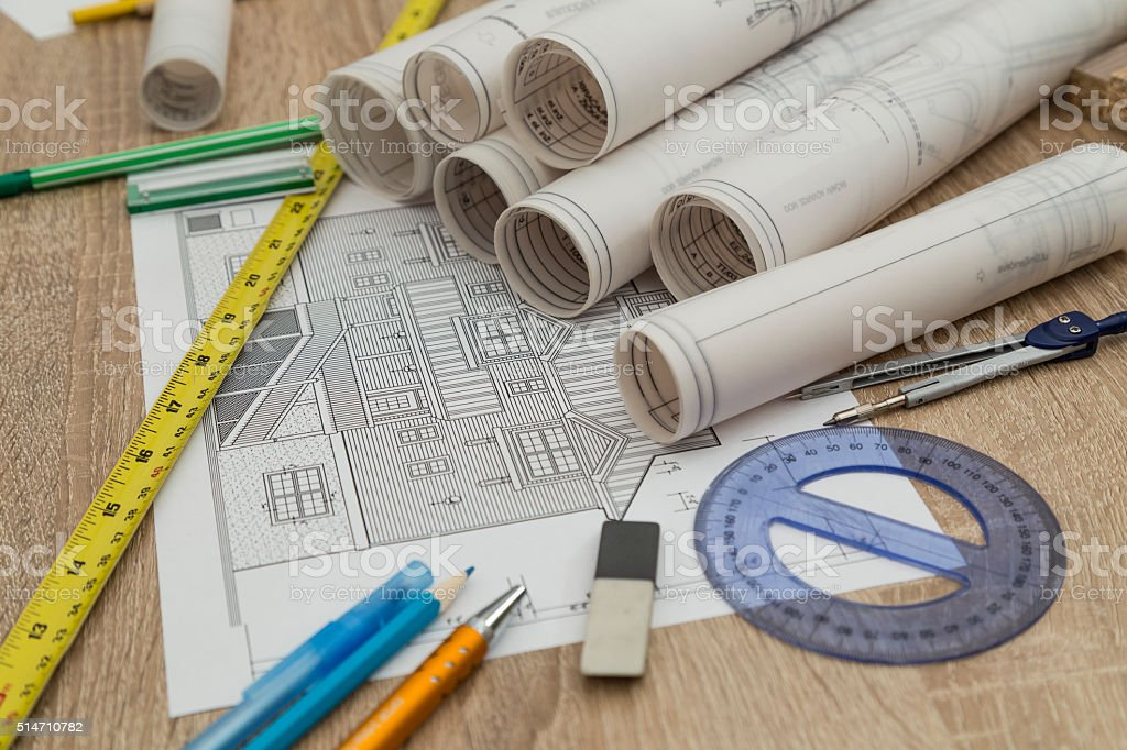 Rolls of blueprints on wooden table stock photo