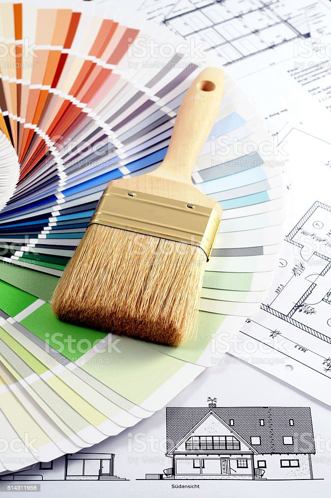 rolls of blueprints with color swatch and paintbrush stock photo