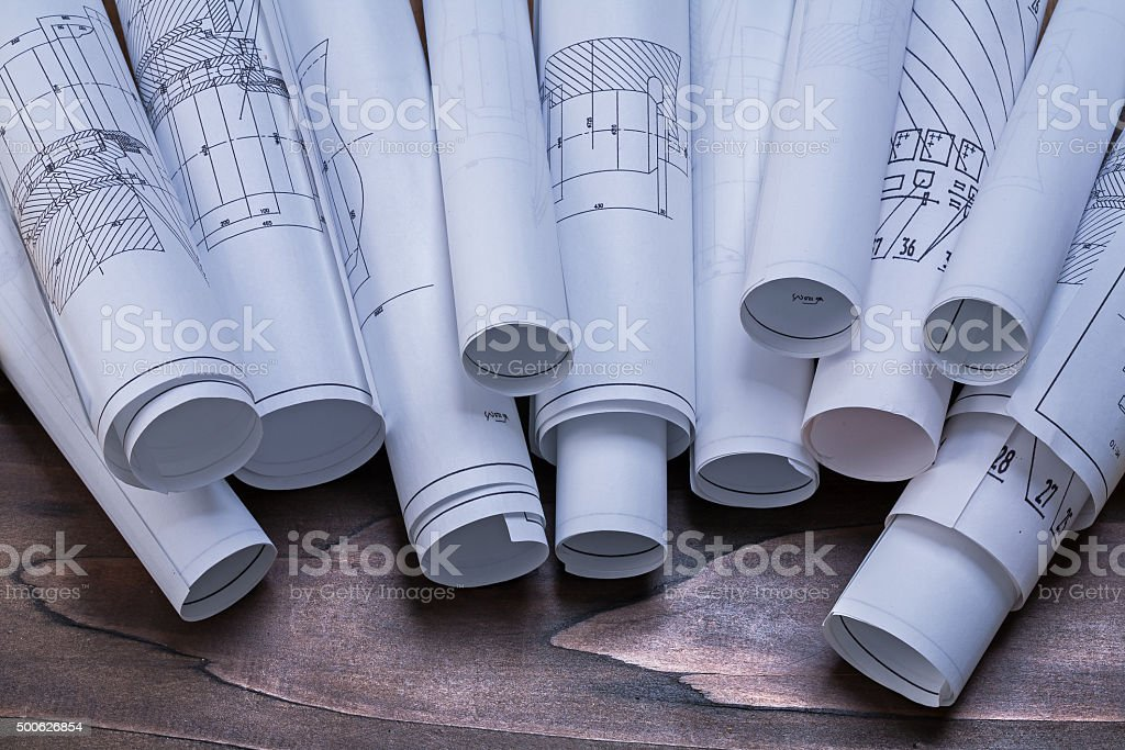 Rolls of construction plans on pine wooden vintage board mainten stock photo