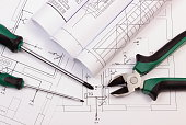Rolls of diagrams and work tools on electrical construction drawing