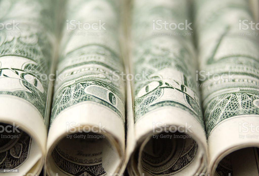 Rolls of dollar bills lined up next to one another stock photo