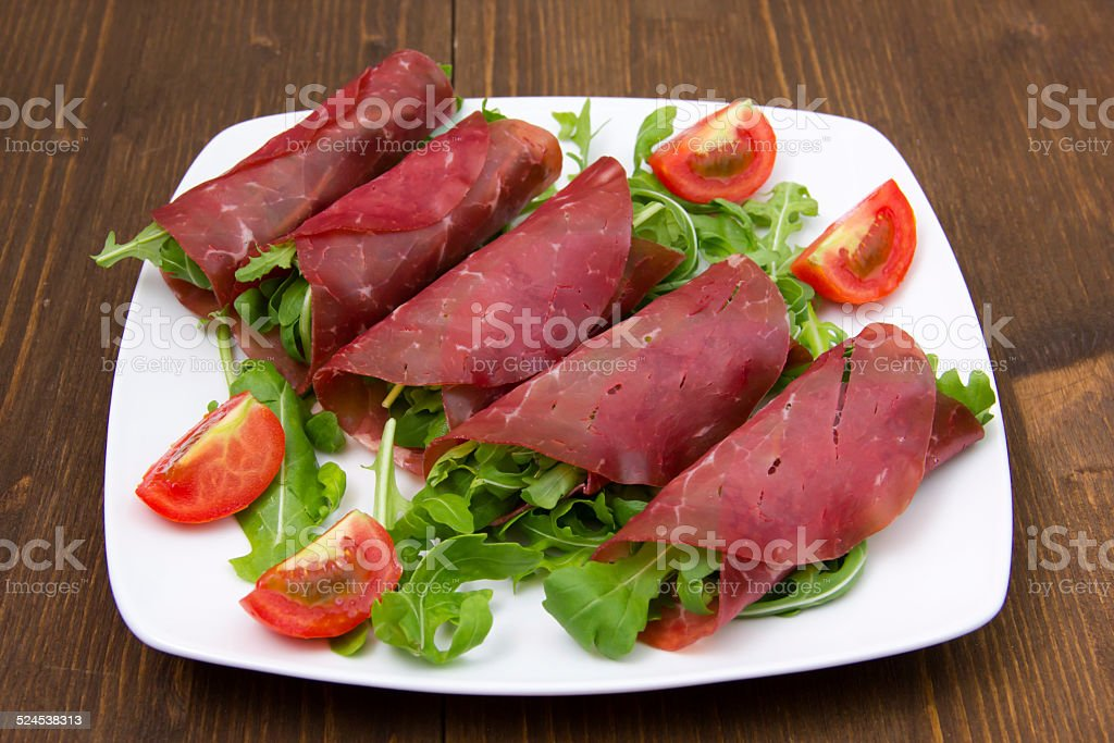 Rolls of dried beef on wood stock photo