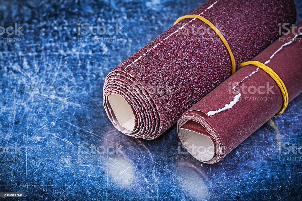 Rolls of emery paper on metallic background abrasive equipment stock photo