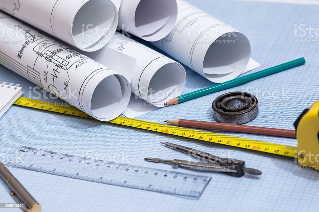rolls of engineering drawings with tools on graph background stock photo