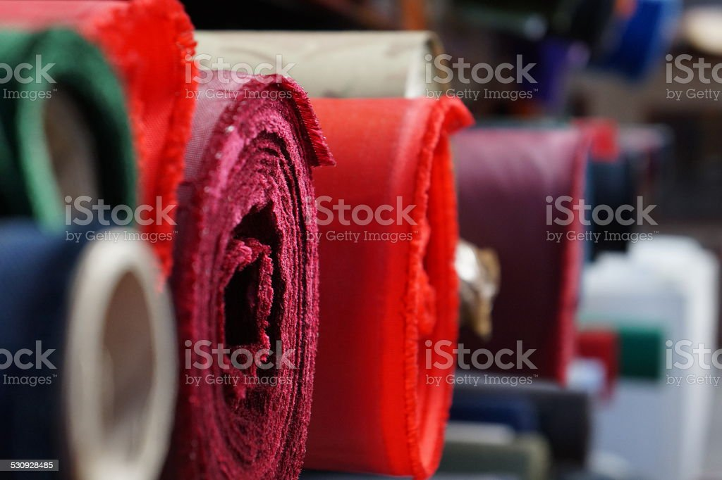 Rolls of material on a shelf stock photo