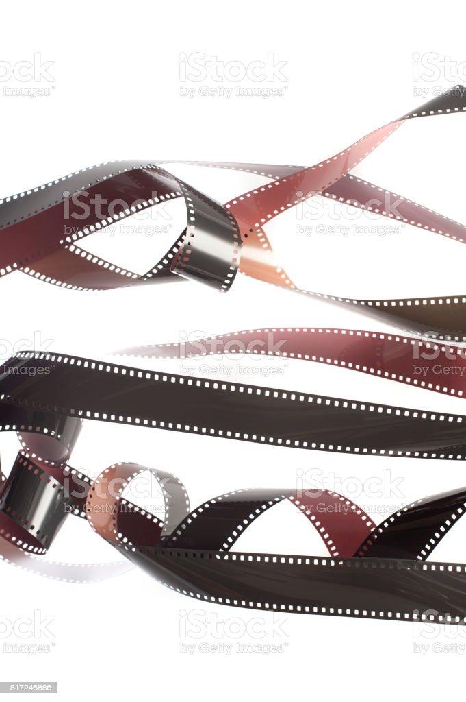 Rolls of tangled 35mm film over white stock photo