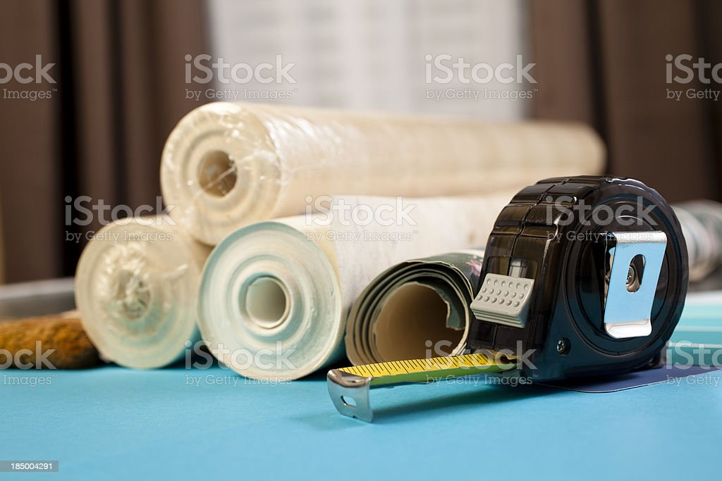 Rolls of wallpaper in home and tape measure royalty-free stock photo