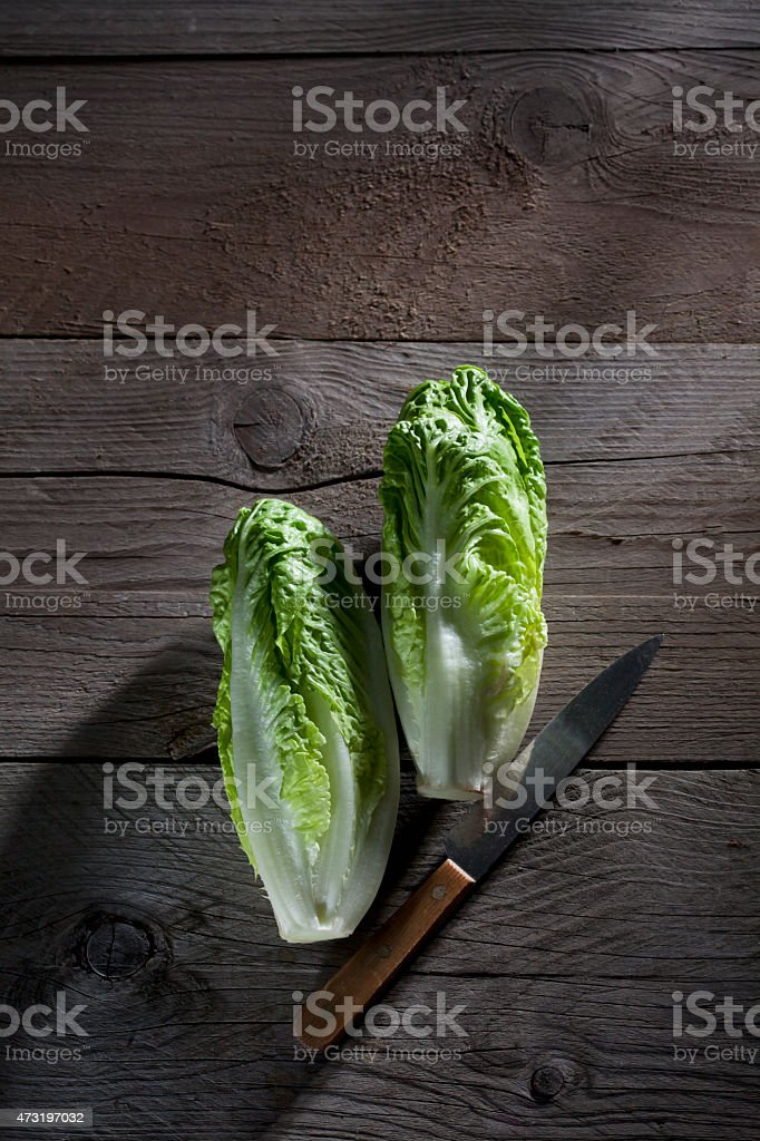 Romaine lettuce and knife on wood stock photo