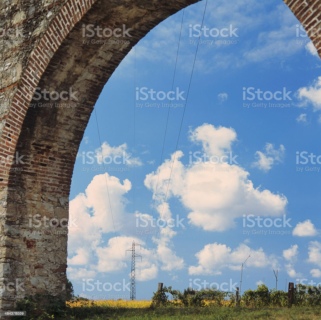 Roman aqueduct and power lines across the fields stock photo