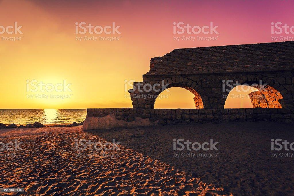 Roman aqueduct in ancient city Caesarea at sunset. Israel. stock photo