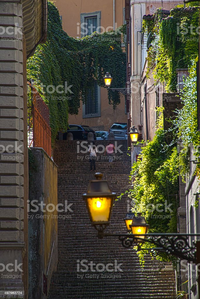 Roman street view with steps plants sun and lights stock photo
