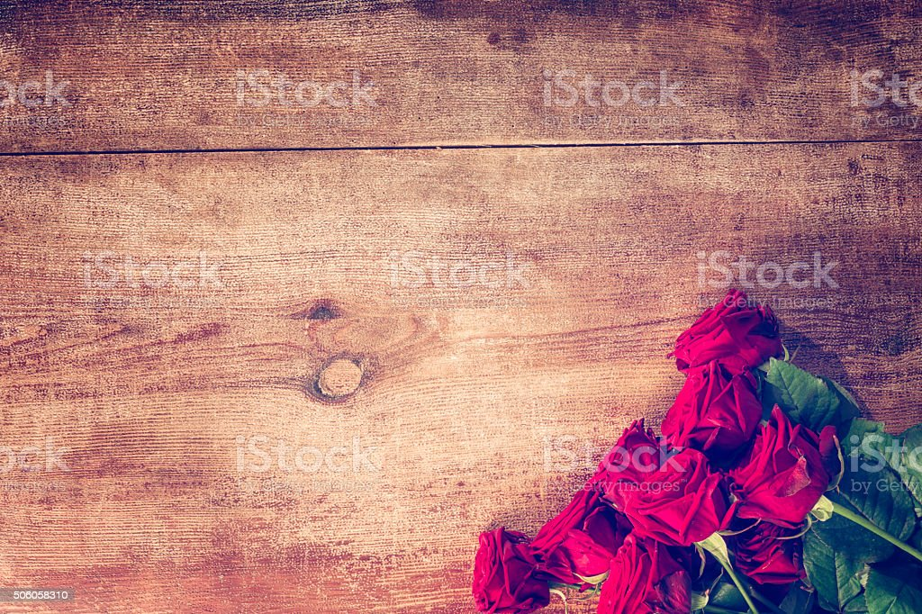 Romantic Bouquet of Red Roses on Wooden Background stock photo