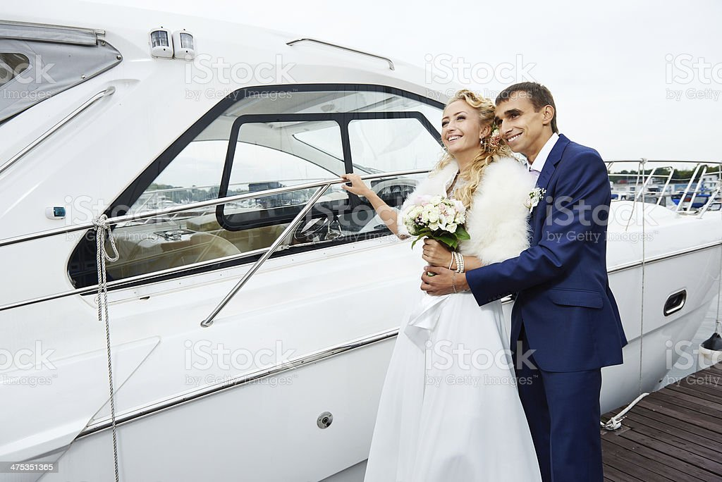 Romantic bride and groom on the pier with yacht royalty-free stock photo