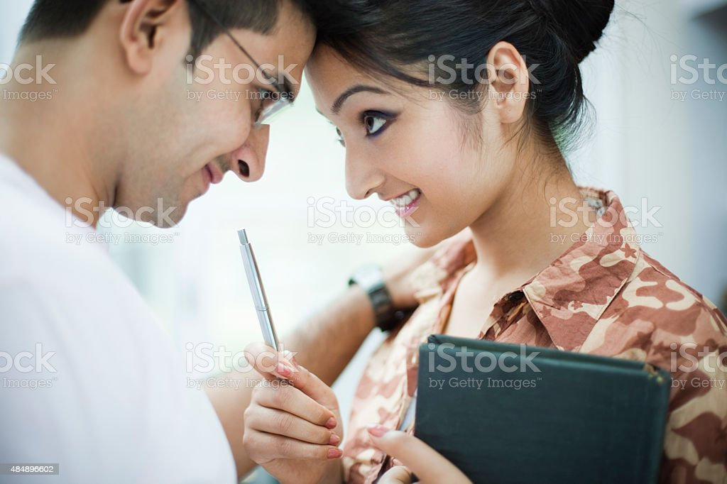 Romantic business woman and man touching forehead with each other. stock photo