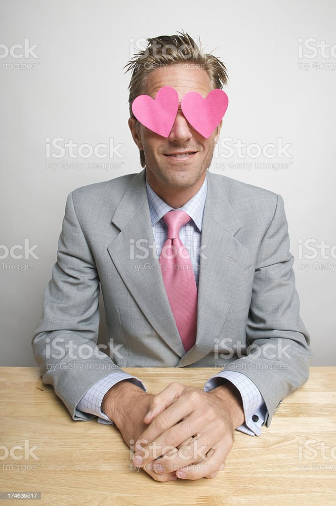 Romantic Businessman Wearing Pink Hearts Sitting at Desk stock photo