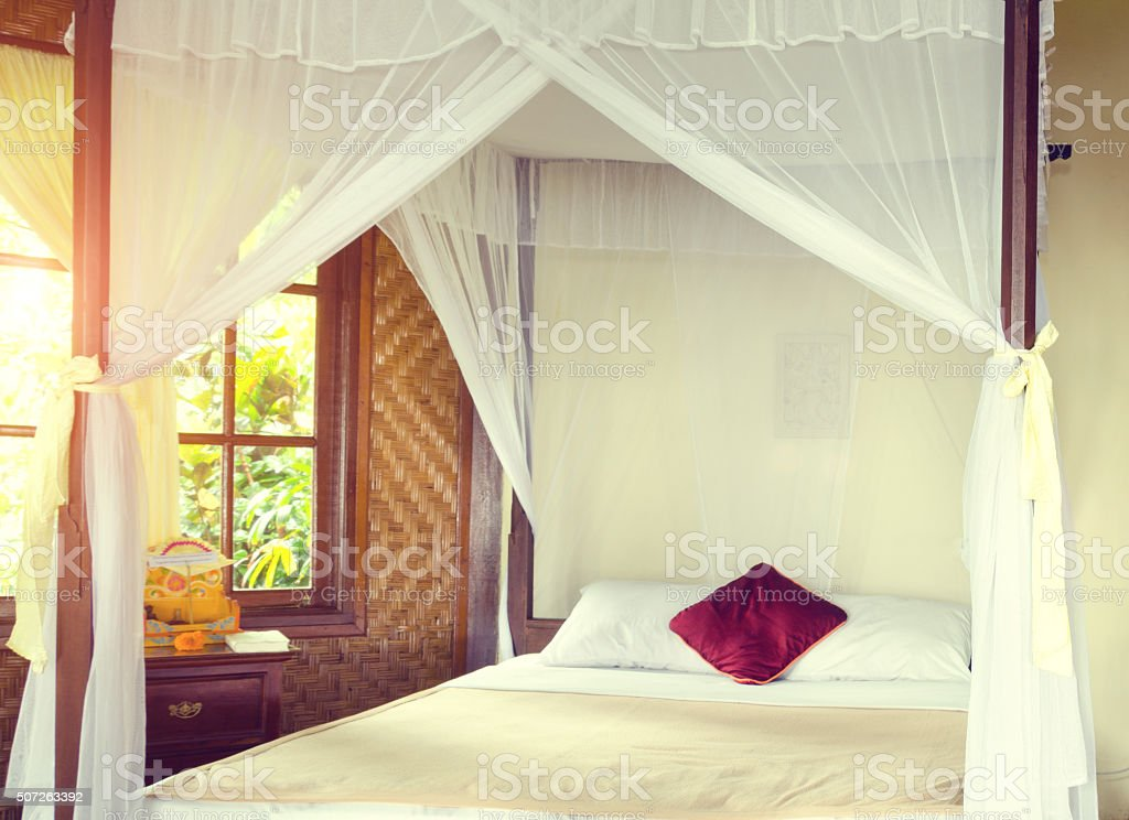 romantic canopy bed with red pillow in jungle stock photo