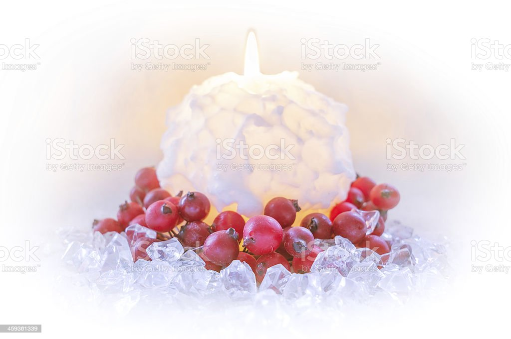 romantic christmas candle surrounded by ice and red berries stock photo