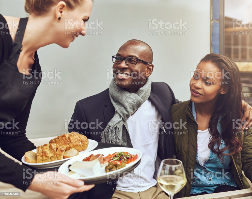 Romantic couple being served dinner stock photo