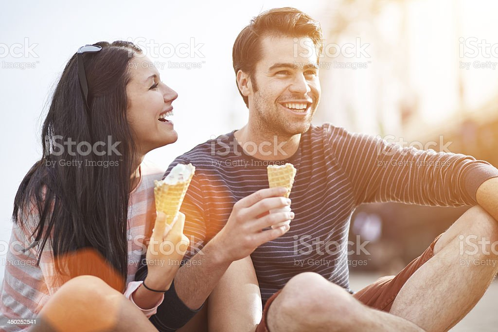 romantic couple eating ice cream at park stock photo