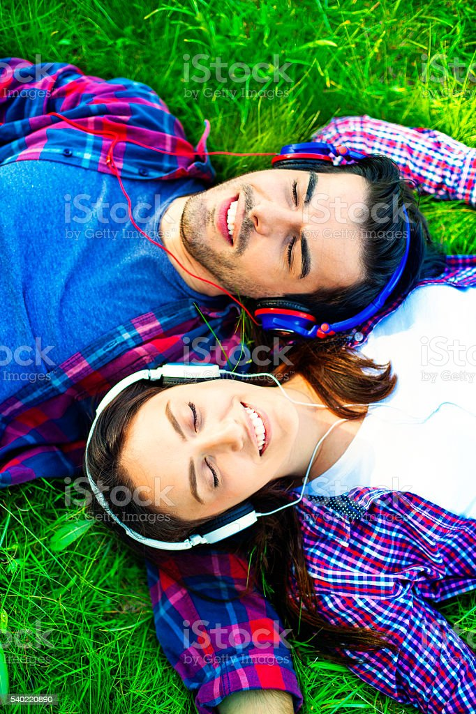 Romantic couple enjoying listening to music stock photo
