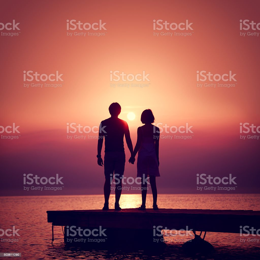 Romantic Couple Enjoying Sunset at Sea. stock photo