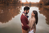 Romantic couple flirting near the river during autumn day.