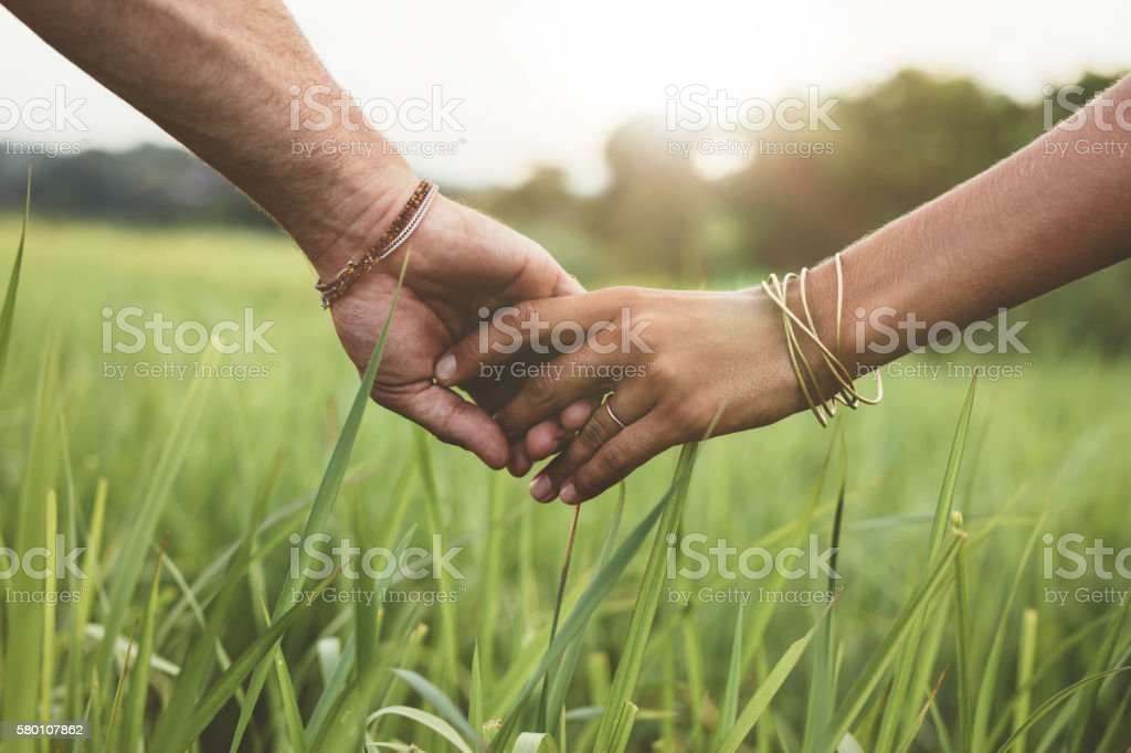 Romantic couple holding hands in a field stock photo