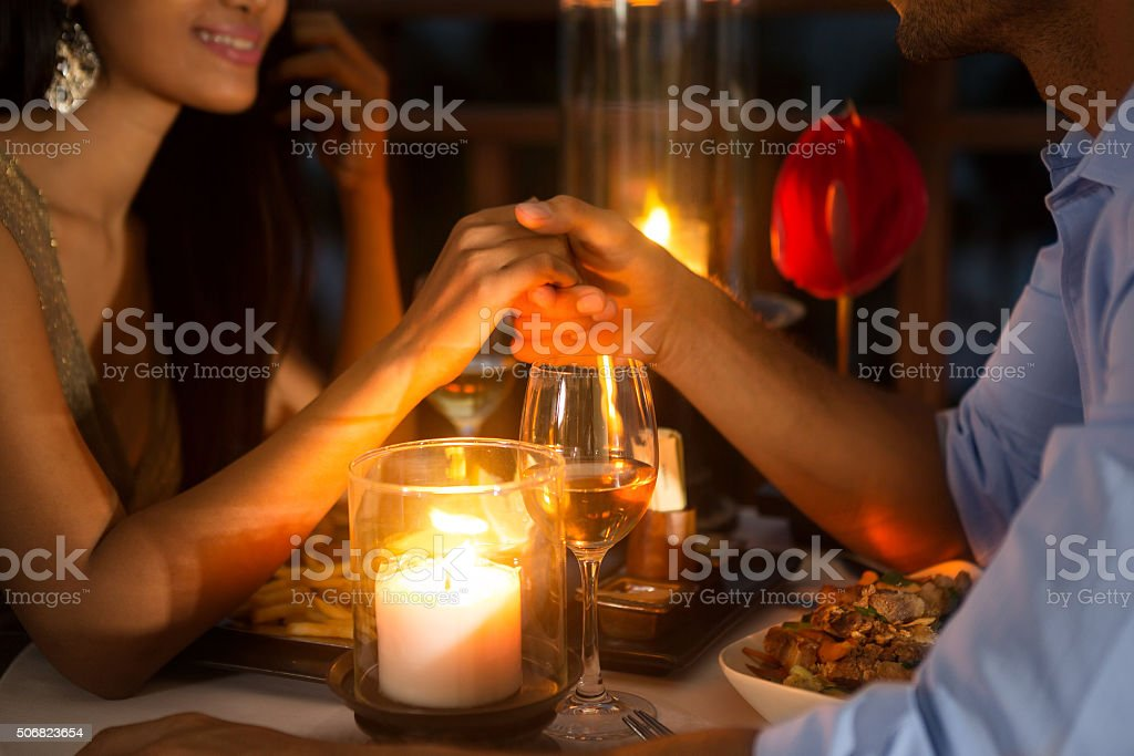 Romantic couple holding hands together over candlelight stock photo