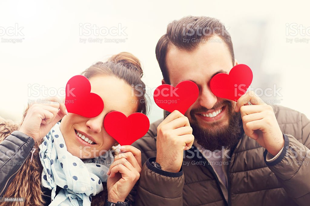 Romantic couple holding hearts stock photo