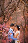 Romantic couple hugging in autumn park. Happy bride and groom